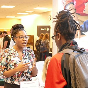 Student speaks to recruiter at career event.