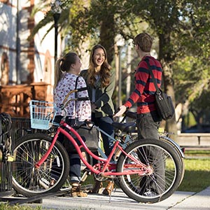 Three students stand in front of bike rack, fourth student skates by on skateboard.