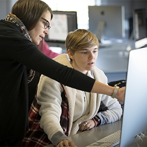 Student being instructed by professor, in front of computer