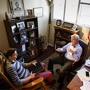Student and professor seated in office.
