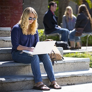 Student seated on steps with laptop in hand.