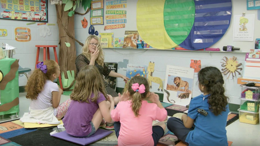 Elementary school students sit with teacher, conversing in sign language.
