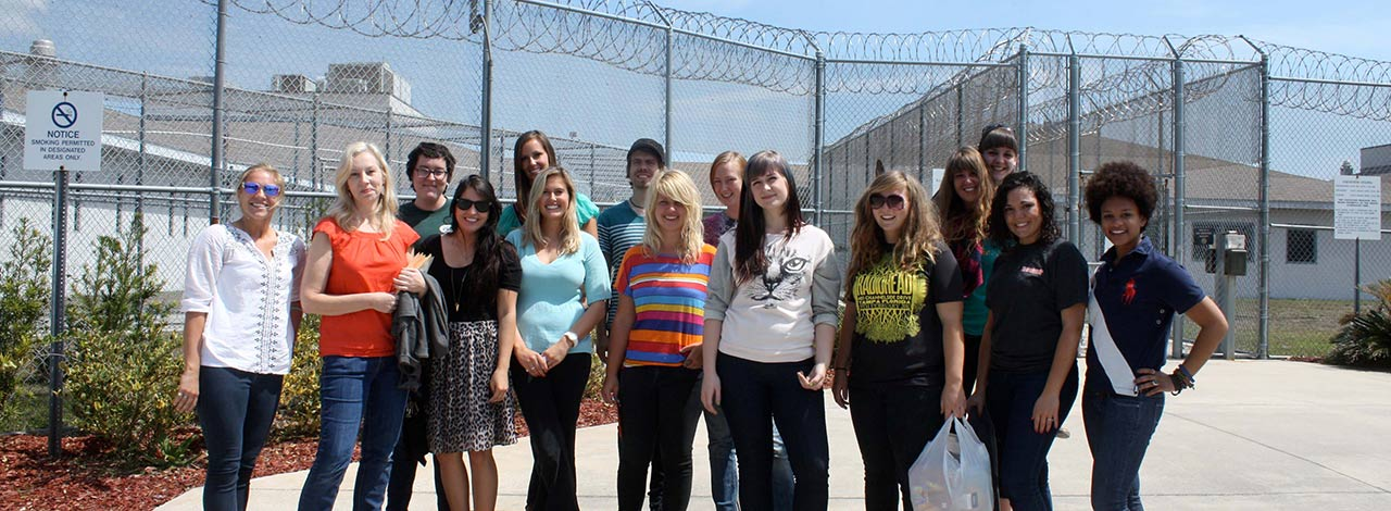 Image of students and art professor Leslee Robison working in the local prison with youth offenders.