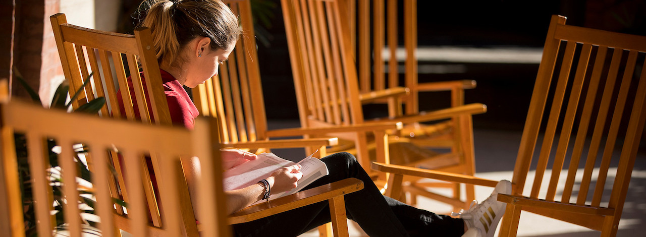 Student sits in rocking chair reading textbook.