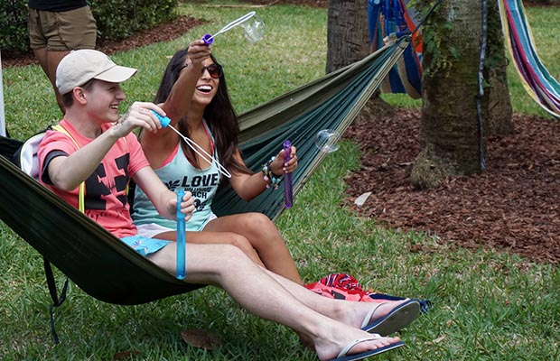 Two students sit in hammock, blowing bubbles.