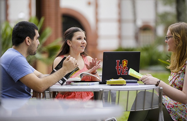 Three students seated at outdoor table talking.