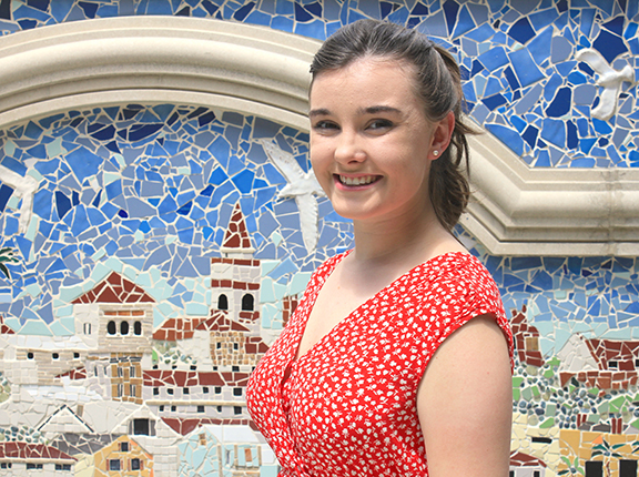 History and English major Shannon Schmidt in front of colorful mosaic
