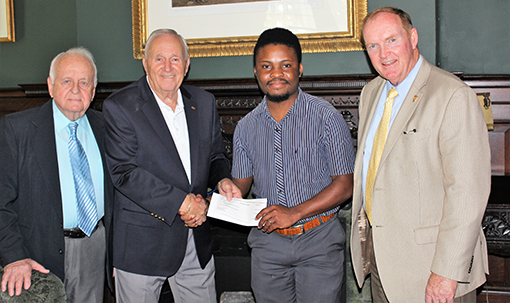 Nick Cuffy shakes the hand of a retired faculty member while receiving his SASS scholarship