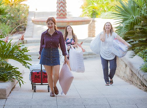 A picture of three people moving into Flagler College on move in day.
